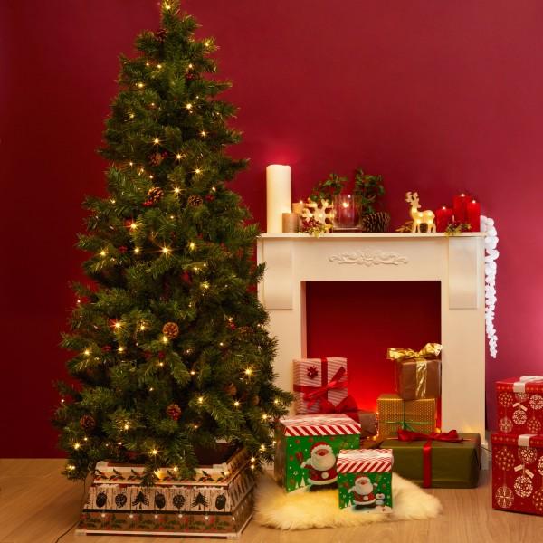 Albero di natale Meribel con pigne e bacche rosse ambientato e addobbato con luci e decorazioni