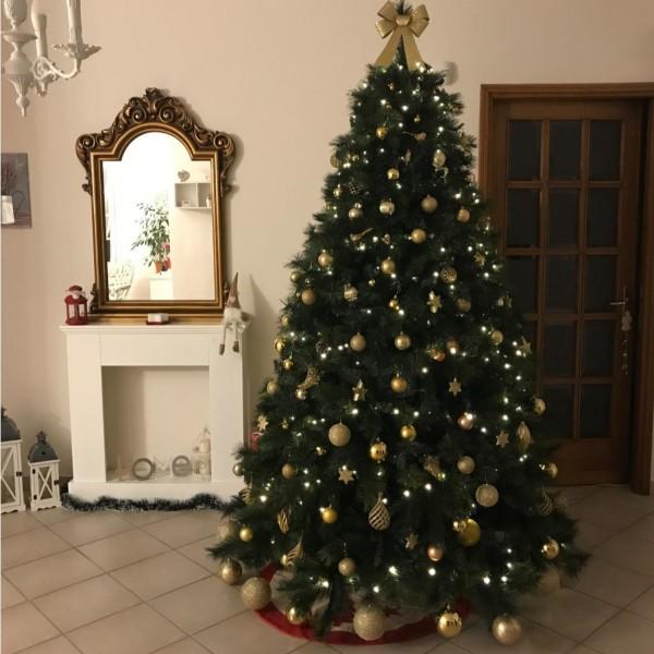 Salotto decorato con albero di natale foltissimo verde con addobbi luci festoni Milton Xone